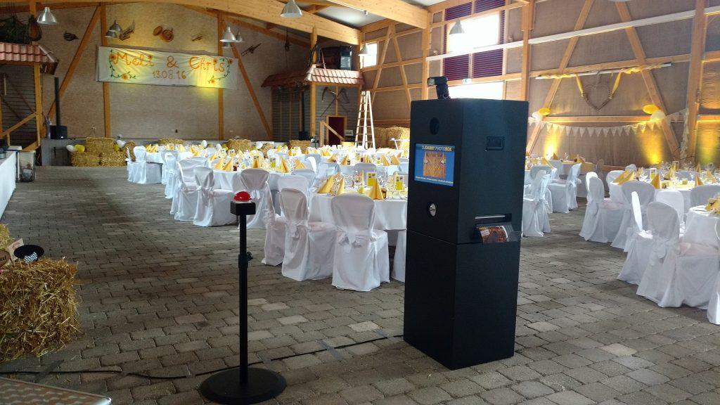 Das Bild zeigt die Musikantenscheune in Nehren im Vordergrund die Photobox im Hintergrund die Ambientebeleuchtung in Farbe gelb